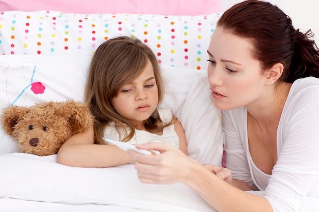 Mãe que toma a temperatura da filha doente