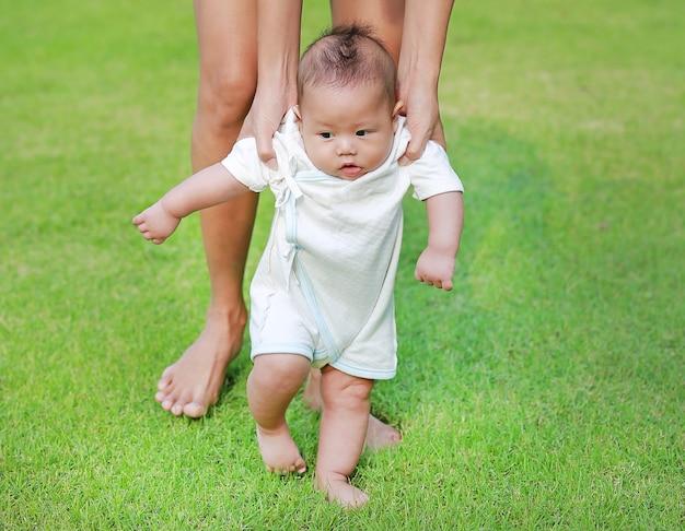 Mãe que treina seu bebê infantil para andar primeiras etapas no jardim da grama verde.