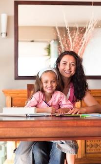 Mãe radiante ajudando sua filha a fazer a lição de casa