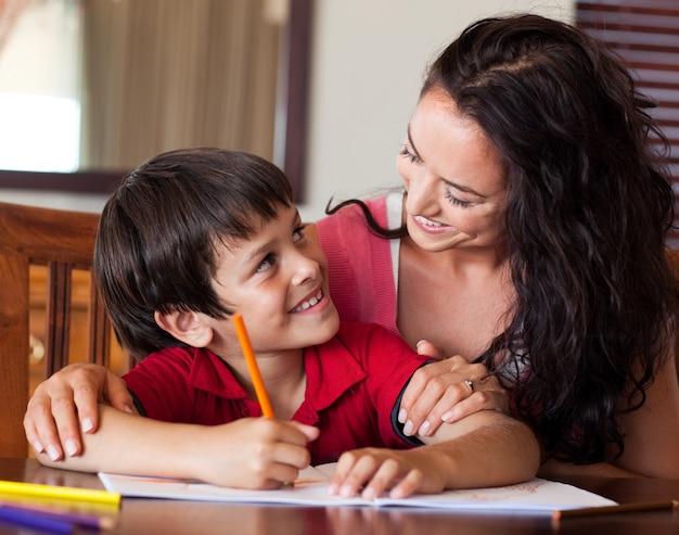 Mãe radiante que ajuda seu filho a fazer a lição de casa
