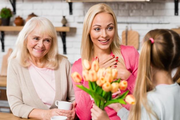 Mãe recebendo um buquê de flores da filha