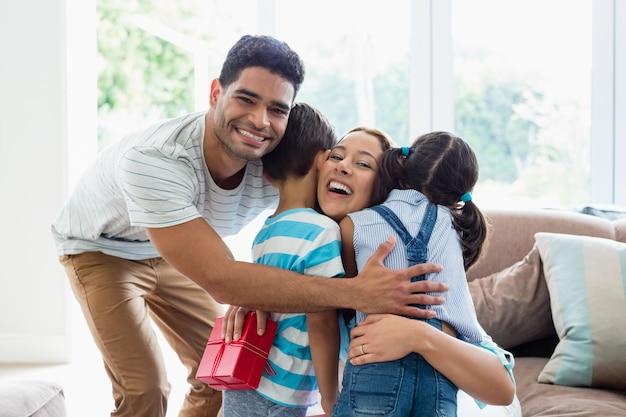 Mãe recebendo um presente de seus filhos e marido na sala de estar