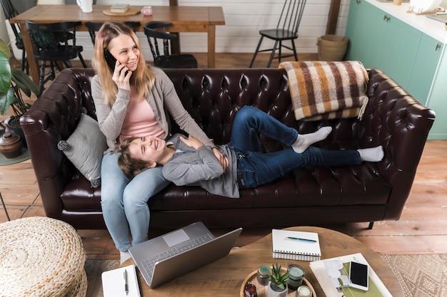 Mãe relaxante junto com o filho no sofá