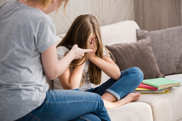 Mãe repreende a filha chorando da escola por dever de casa