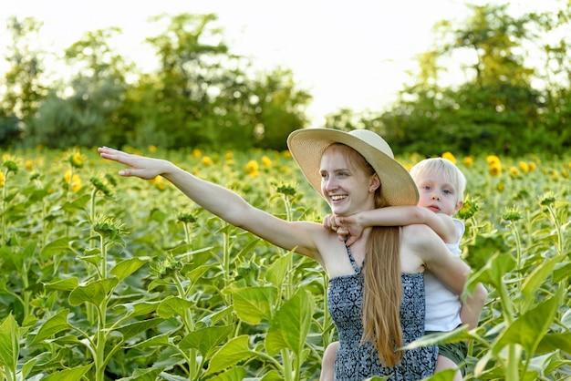Mãe rindo feliz dando cavalinho filho da criança andar no campo de girassóis florescendo verde