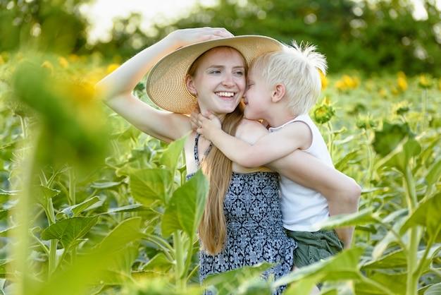 Mãe rindo feliz dando criança filho cavalinho de campo de girassóis florescendo verde