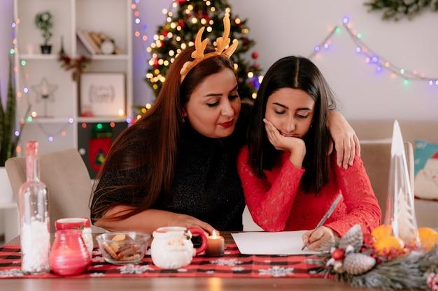 Mãe satisfeita com bandana de rena olha para a carta que sua filha está escrevendo, sentada à mesa, aproveitando o natal em casa