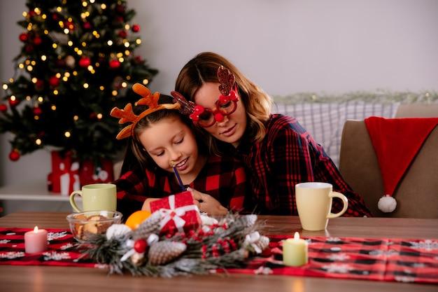 Mãe satisfeita com óculos de rena ensina a filha a desenhar no caderno, sentada à mesa, aproveitando o natal em casa