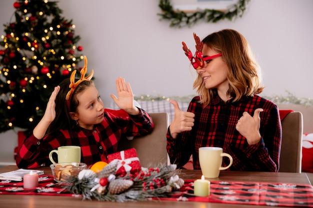 Mãe satisfeita com óculos de rena manuseando olhando para a filha sentada à mesa, aproveitando o natal em casa