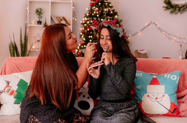 Mãe satisfeita fazendo maquiagem para a filha com coroa de azevinho sentada no sofá aproveitando o natal em casa
