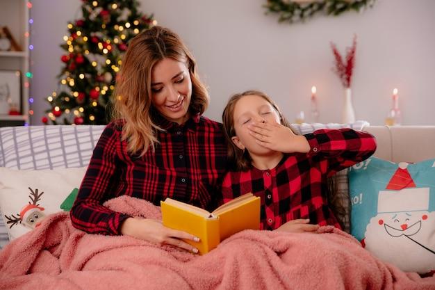 Mãe satisfeita lendo livro e filha sonolenta bocejando coberta com um cobertor sentada no sofá curtindo o natal em casa