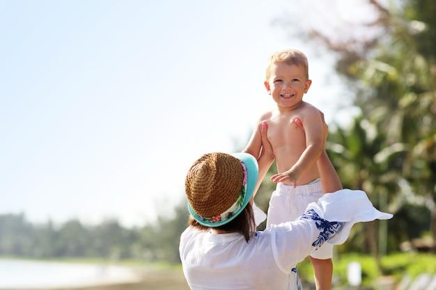 Mãe se divertindo na praia com seu filho pequeno