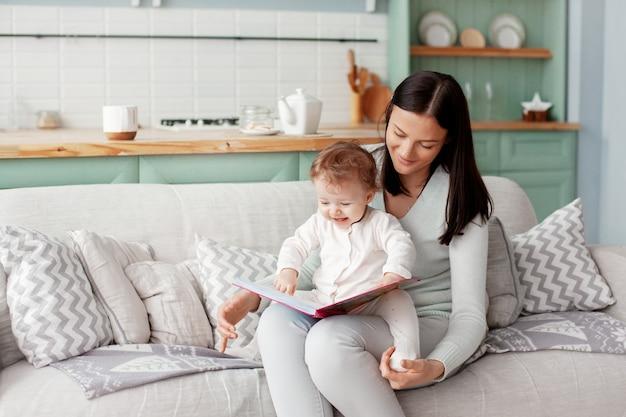 Mãe se senta em um sofá com uma criança, lê um livro e olha fotos brilhantes