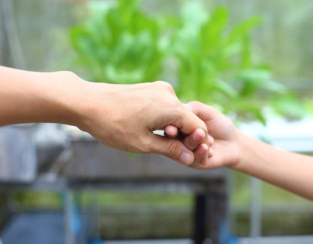 Mãe segura a mão do filho para ajudar e caminhar juntos