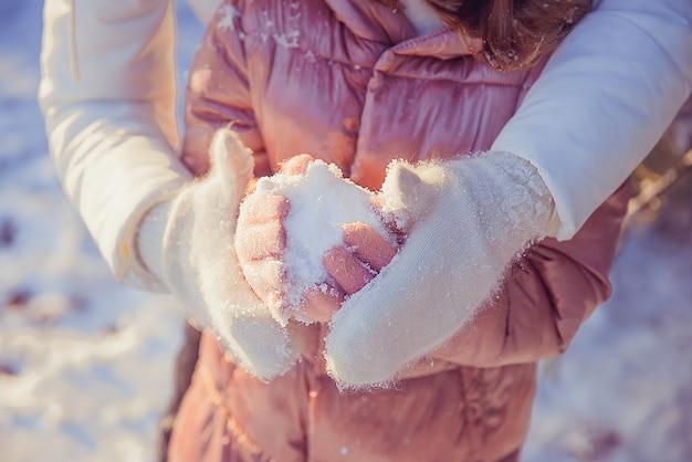 Mãe segura as mãos da filha em luvas de pele na rua na neve do inverno