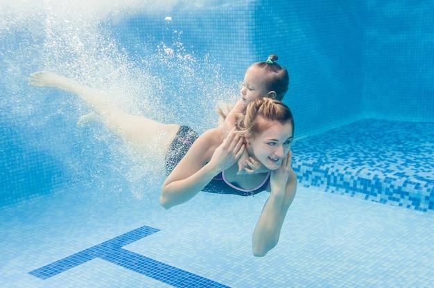 Mãe segura bebê, filha aprende a nadar na aula de natação, mergulhar na água com piscina.