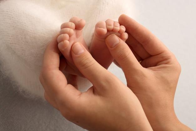 Mãe segura os pés descalços do bebê recém-nascido. pés minúsculos nas mãos de uma mulher. manhã aconchegante em casa. foto de alta qualidade