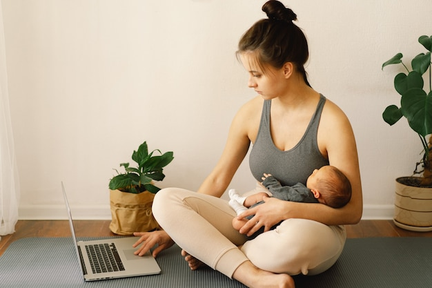 Mãe segura seu filho recém-nascido e trabalha no computador em casa
