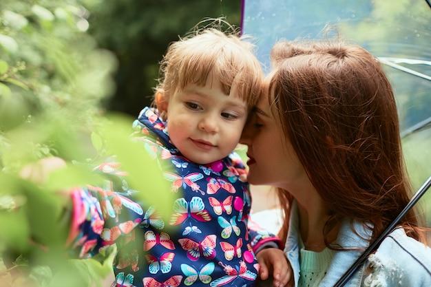 Mãe segura sua filha nas mãos de pé sob o guarda-chuva no parque
