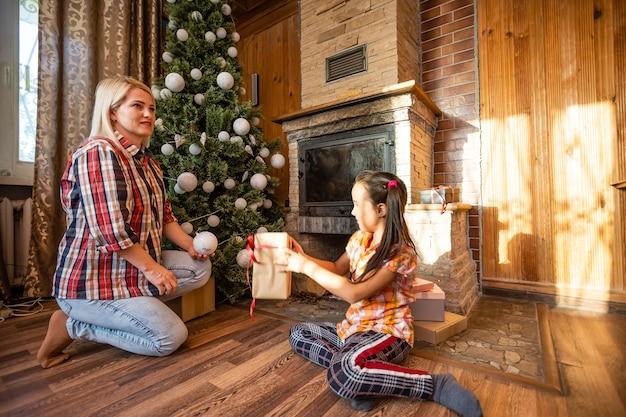 Mãe segura uma filha na árvore de natal em uma noite festiva em uma casa de madeira rústica, ano novo, inverno