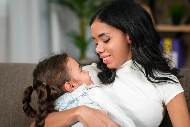 Mãe, segurando a filha como bebê pequeno