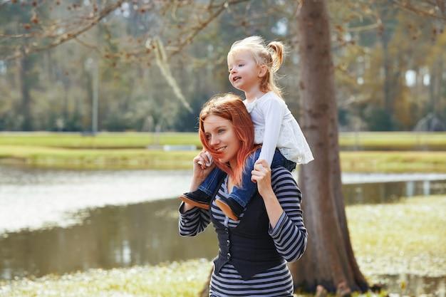 Mãe segurando a filha nos ombros em um lago