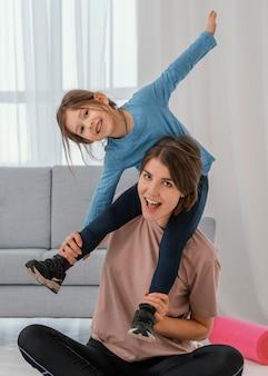 Mãe segurando a garota nos ombros, tiro médio