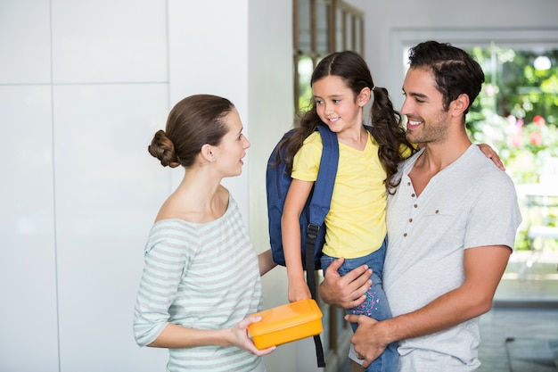 Mãe, segurando a lancheira com o pai carregando filha