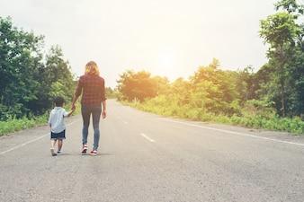 Mãe segurando a mão de seu filho no dia de verão andando na rua