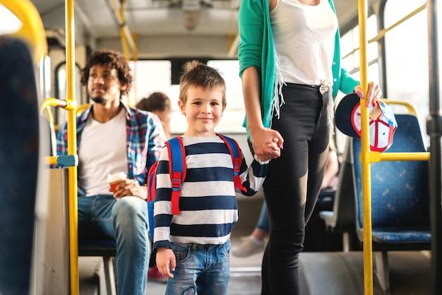 Mãe, segurando a mão do filho e em pé no transporte público. garoto, olhando para a câmera.