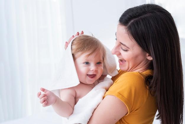 Mãe, segurando bebê com toalha