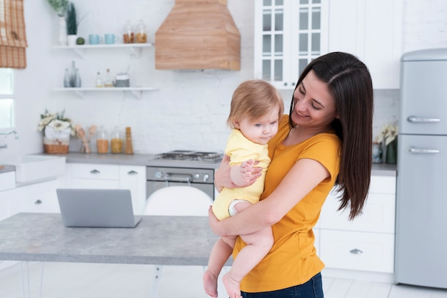 Mãe segurando bebê na cozinha