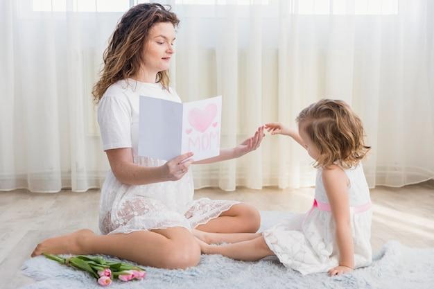 Mãe, segurando, cartão cumprimento, sentando, perto, dela, filha, ligado, tapete, casa