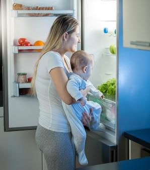 Mãe segurando filho bebê e olhando dentro da geladeira à noite