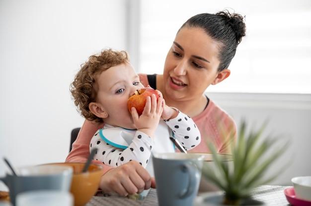 Mãe segurando filho enquanto come
