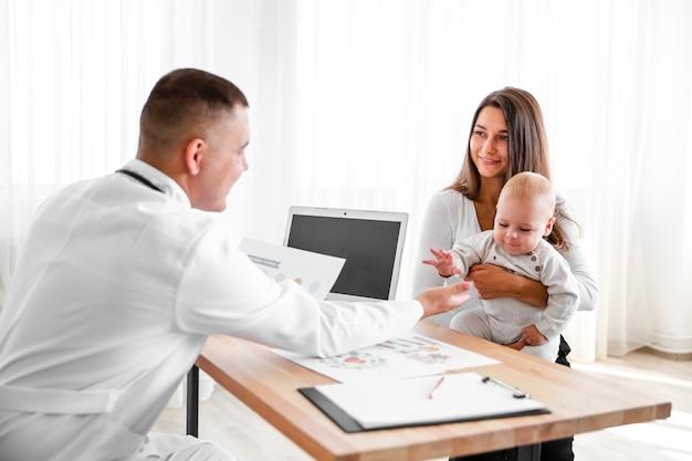 Mãe, segurando o bebê e olhando para o médico