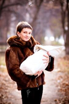 Mãe, segurando o bebê nos braços, embrulhado em um cobertor. efeito de foco suave.