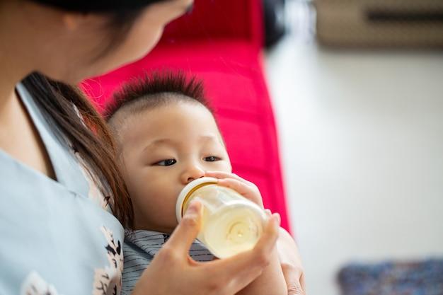 Mãe segurando para alimentar o bebê com leite em casa.