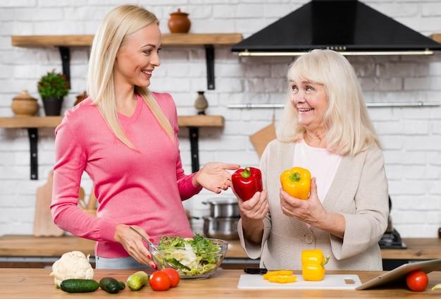 Mãe segurando pimentos e olhando para a filha