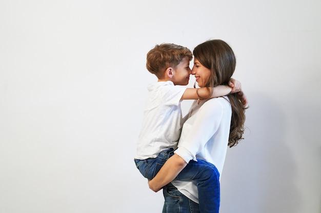 Mãe, segurando seu filho pré-adolescente, sorrindo e olhando nos olhos