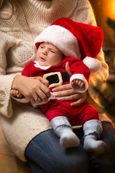 Mãe segurando um lindo bebê recém-nascido fantasiado de papai noel na lareira
