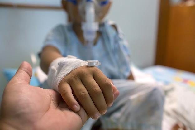 Mãe segurando uma mão de bebê no hospital. amor e preocupação da mãe