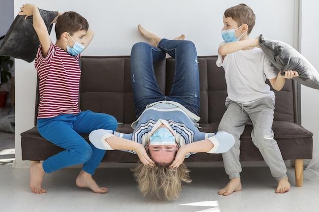 Mãe sendo irritada em casa por crianças que brincam com travesseiros enquanto usam máscaras médicas