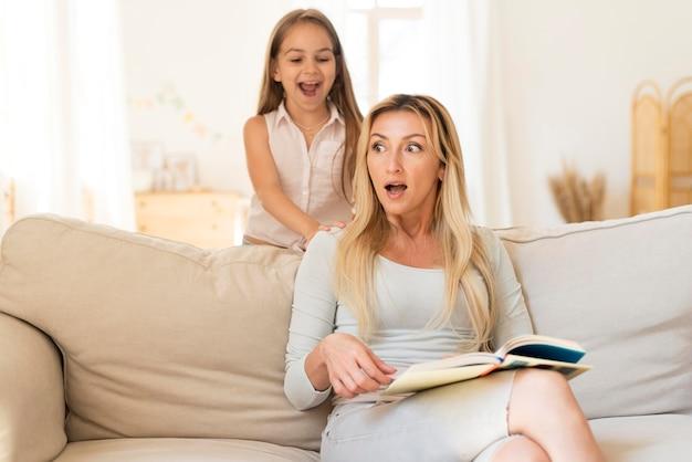 Mãe sendo surpreendida pela filha se esgueirando sobre ela