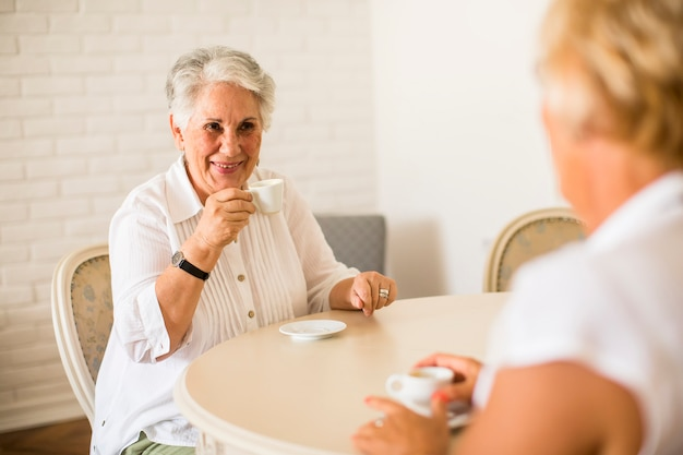 Mãe sênior e filha velha madura, conversando e tomando café no quarto