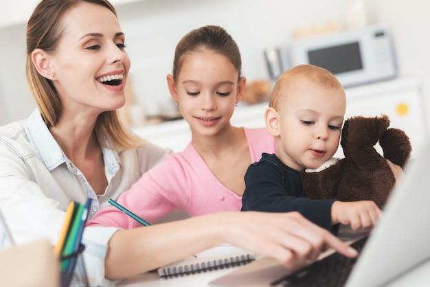 Mãe senta ao lado deles e eles estão sentados no computador.