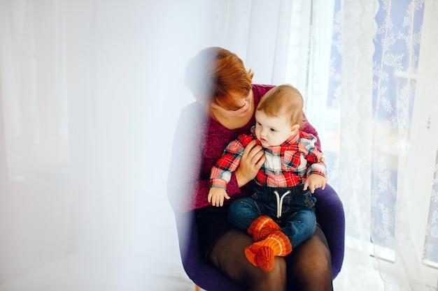 Mãe senta com pequena filha antes da janela