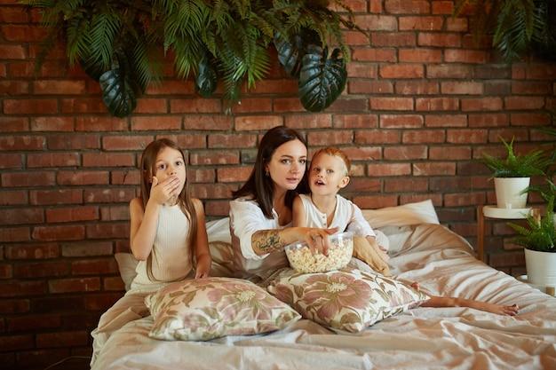 Mãe senta na cama com seu filho e filha e assiste filme
