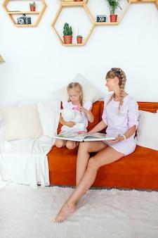 Mãe senta-se em um sofá e lê um livro com a filha em um quarto bonito e brilhante em sua casa