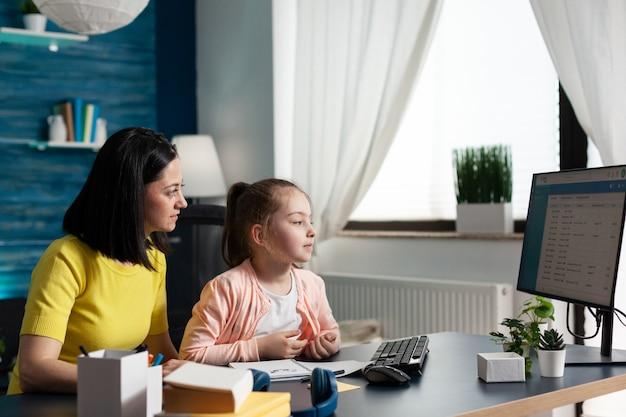 Mãe sentada ao lado da filha fazendo lição de casa juntos
